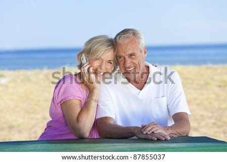 stock photo happy senior man and woman couple sitting together at a table by a beach talking on a cell phone 87855037