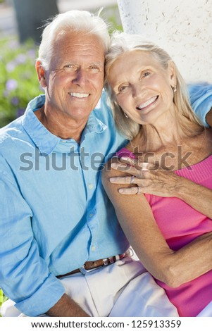 Happy senior man and woman couple sitting together outside in sunshine