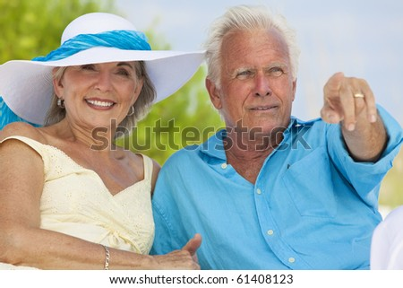 Happy senior man and woman couple sitting together pointing out to sea on a deserted tropical beach