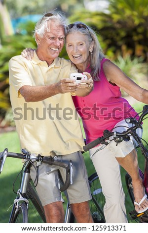 Happy senior man and woman couple together cycling on bicycles taking self portrait picture photograph with digital camera in a sunny green park