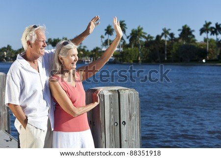 Happy senior man and woman couple together outside in sunshine waving by the sea on a jetty or pier