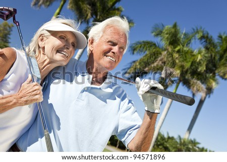 Happy senior man and woman couple together playing golf putting on a green together - stock photo