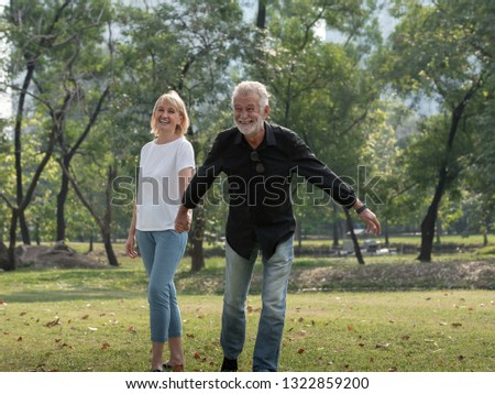 Happy senior man and woman couple walking and holding hands in a park on a sunny day. relax in the forest spring summer time. free time, lifestyle retirement grandparents concept.