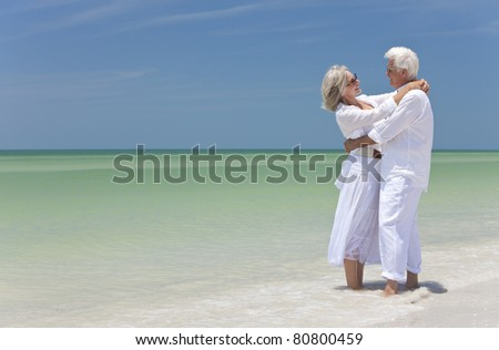 Happy senior man and woman embracing on a deserted tropical beach with bright clear blue sky