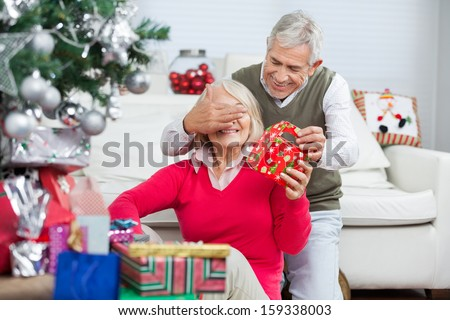Happy senior man covering woman\'s eyes while giving Christmas gift at home