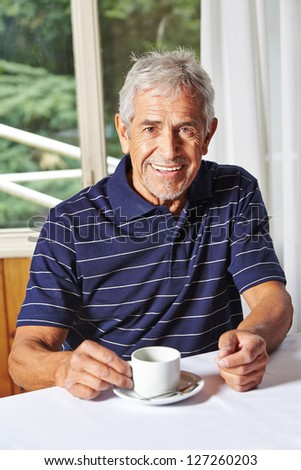 Happy senior man drinking a cup of coffee in a nursing home
