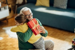 Happy senior man embracing his granddaughter while receiving a gift on Christmas at home.