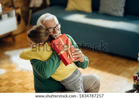 Happy senior man embracing his granddaughter while receiving a gift on Christmas at home.  Foto stock ©