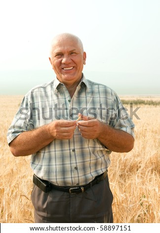 Happy senior man in field with ears of barley and wheat