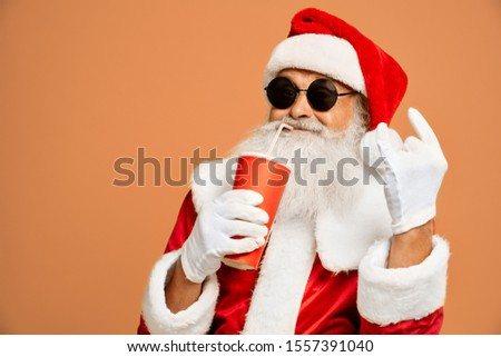 Happy senior man in traditional Santa suit with real grey beard drinking from red paper cup with straw and showing two horn sign. Santa Claus in black trendy sunglasses enjoying free time.
