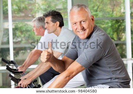 Happy senior man on bike holding thumbs up in fitness center