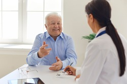 Happy senior man talking to doctor during visit to hospital office, thanking her for quick painless recovery. Clinician filling out medical history form while listening to old patient during interview
