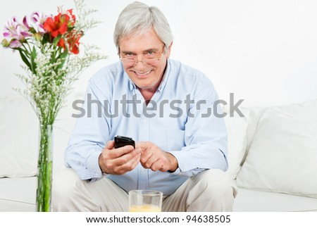 Happy senior man using a smartphone on the couch