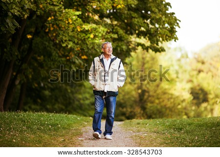 Happy senior man walking and relaxing in park