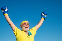 Happy Senior man wearing boxing gloves. Portrait of a determined senior boxer over blue sky background. Healthy fighter senior old man boxing gloves