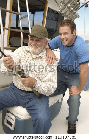 Happy senior man with grandson fishing together on yacht
