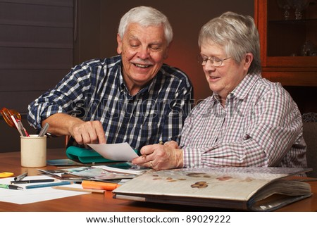 Happy senior married couple sharing memories while  working on family photo  album together. Horizontal format.