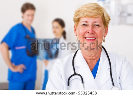 happy senior medical doctor, background is her young colleagues looking at x ray