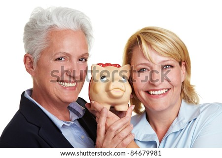 Happy senior mother and adult daughter holding a piggy bank