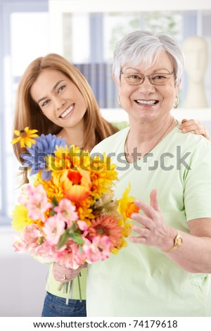 Happy senior mother and daughter smiling at mother\'s day, holding flowers.?