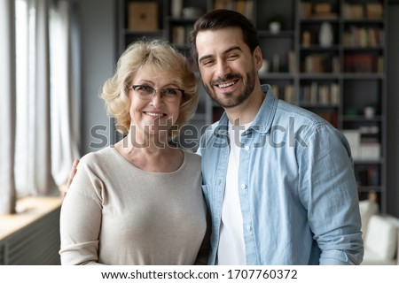 Happy senior mother in eyeglasses and bearded grown up son standing posing looking at camera. Different ages, multi-generational family portrait, next generation and offspring, familial values concept
