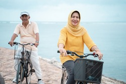 happy senior muslim couple exercising riding bicycle together at the beach