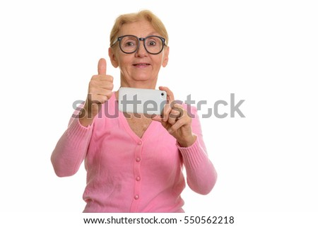 Happy senior nerd woman smiling while taking picture with mobile phone and giving thumb up isolated against white background