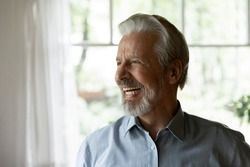 Happy senior 70s aged man looking away and laughing at funny joke. Healthy mature older person having fun at home, enjoying retirement, having great health, getting good news. Elderly OAP age concept