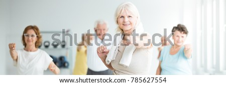 Happy senior sportswoman with a towel around her neck exercising with friends in a fitness studio #785627554