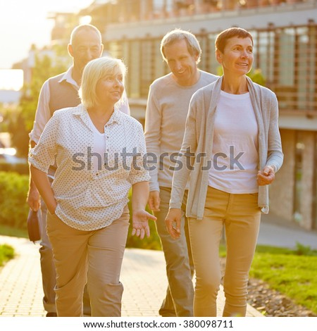 Happy senior travel group walking in a city in summer