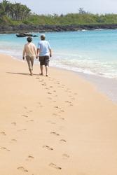 happy senior walking on the beach with footprint
