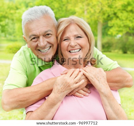 Happy senior woman and man enjoying in the park. - stock photo