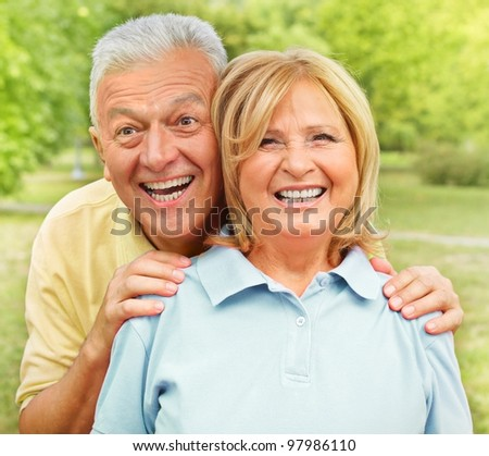 Happy senior woman and man enjoying in the park.