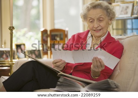 Happy senior woman at home holding a group of photos