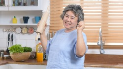 Happy senior woman dancing in kitchen, Elderly retirement female with happiness expression in lifestyle