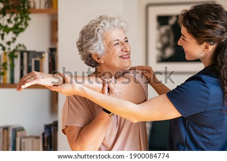 Happy senior woman doing exercise at home with physiotherapist. Old retired lady doing stretching arms at home with the help of a personal trainer during a rehabilitation session.