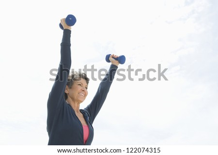 Happy senior woman exercising with two dumbbells against sky