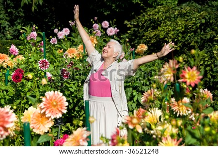 Happy senior woman expressing positivity, happiness, joy in the garden full of flowers