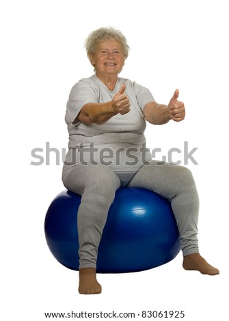 Happy senior woman gives OK on a fitball, on white background