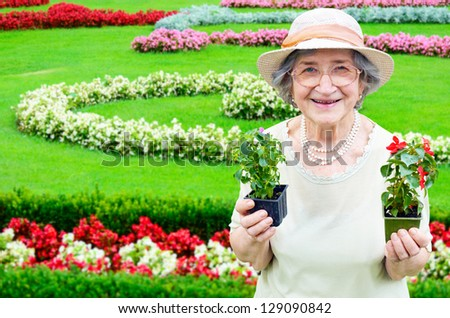 Happy senior woman holding flowers in garden