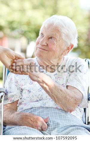 Happy senior woman holding hands with her caretaker