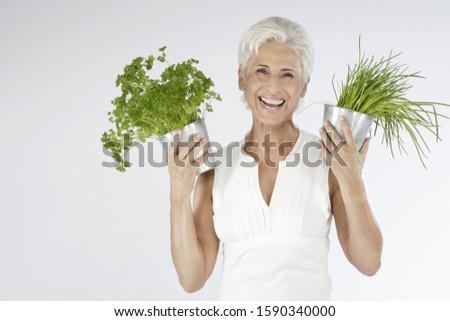 Happy senior woman holding plants