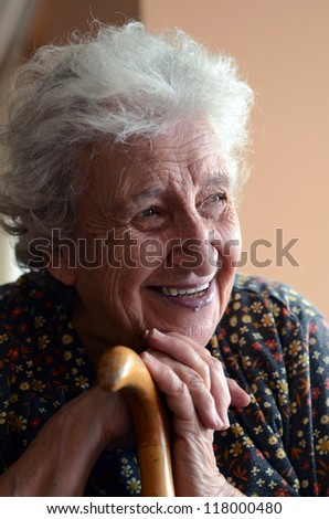 happy senior woman holding wooden cane