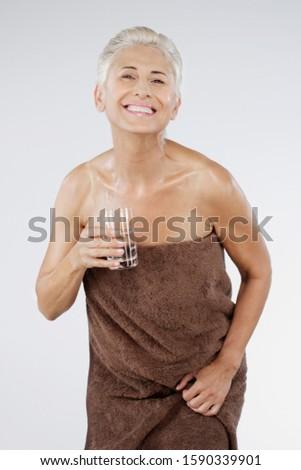Happy senior woman in towel drinking water