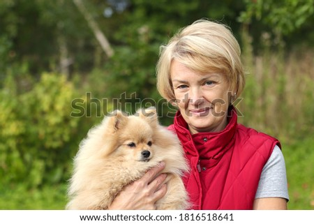 Happy senior woman is holding her Pomeranian Spitz dog on hands outdoors and smiling. People love pets ストックフォト ©