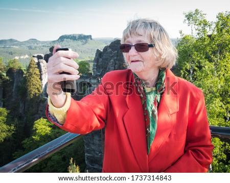 Happy senior woman is taking a selfie at Bastei bridge in Saxon Switzerland ストックフォト ©