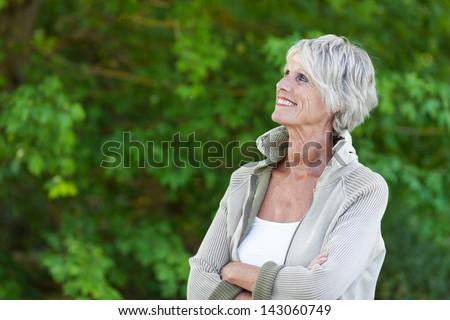 Happy senior woman looking at the beautiful trees
