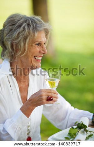 Happy senior woman looking away while holding wineglass in lawn