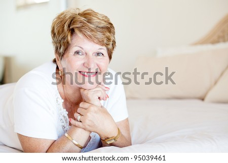 happy senior woman lying on bed - stock photo