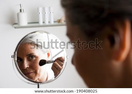 Happy senior woman making up